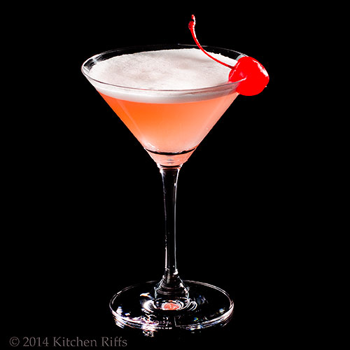 Pink Lady Cocktail with maraschino cherry garnish