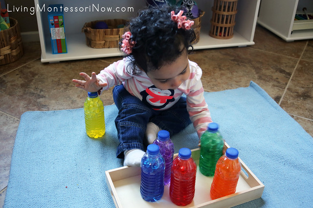 Taking water-bead sensory bottles off the tray