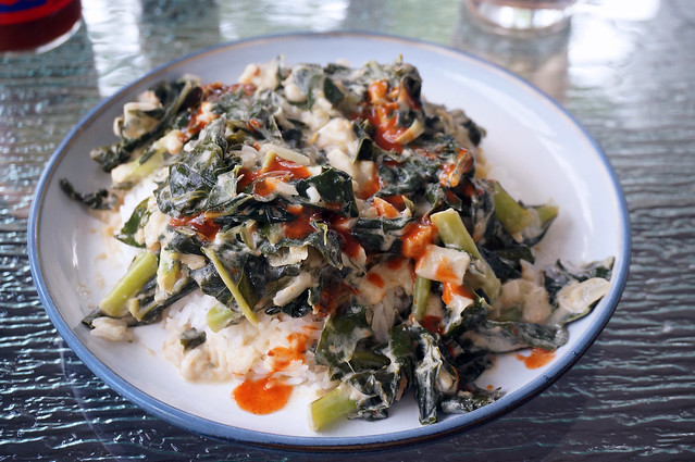 Collards with coconut and peanut butter, drizzled with hot sauce, on a glass patio table; the edges of bottles and water glasses are barely visible at the edges of the picture