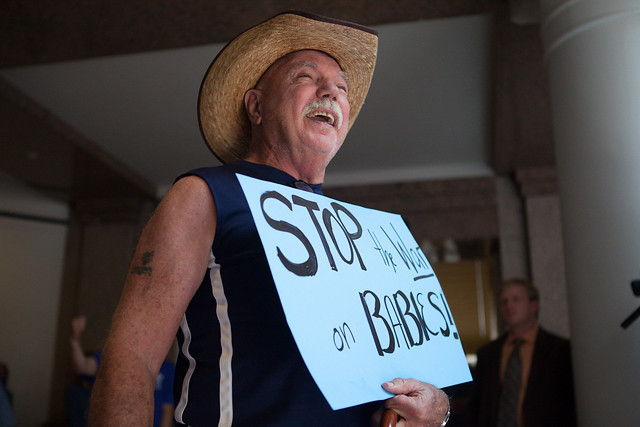 "A man in a cowboy hat holds a sign that reads ""stop the war on babies"""