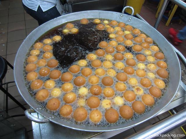 Buñuelos being deep fried in a vat of oil