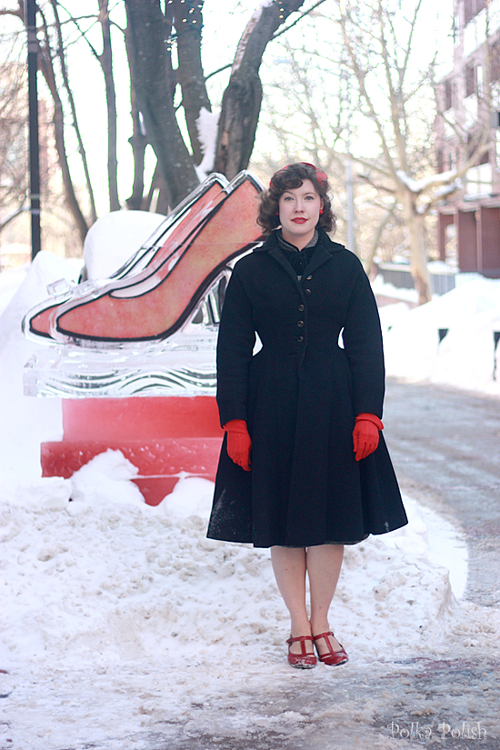 Posing next to an ice sculpure of red high heels wearing red shoes, gloves, and hat with a black 1950s princess coat