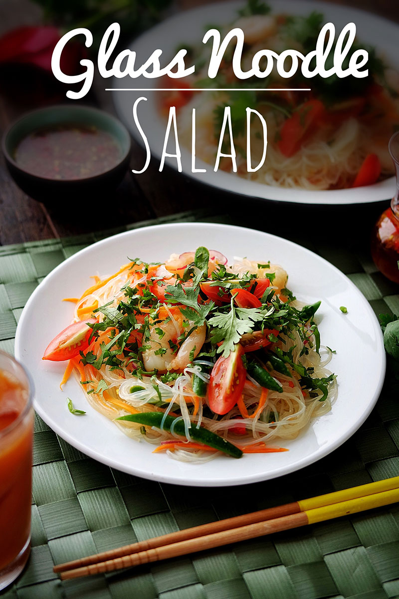 Thai Glass Noodle Salad on a white plate, with yellow chopsticks and a glass of Thai Iced Tea on the side