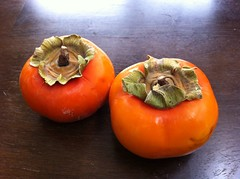 Two persimmons on a table.