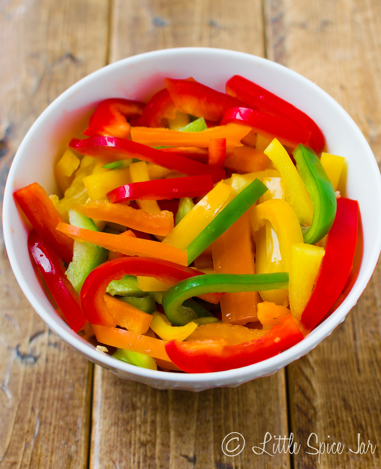 multi colored bell peppers in strips in white bowl on wood surface