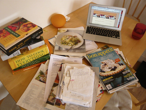 Stacks of magazines and cookbooks in front of an open laptop
