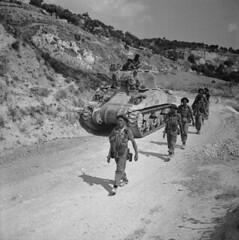 Personnel of Princess Patricia's Canadian Light Infantry advancing past a Sherman tank, near Valguarnera, Italy... / Des membres du Princess Patricia's Canadian Light Infantry passent devant un char Sherman près de Valguarnera (Italie)...
