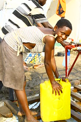 Woman collecting water from a tap stand