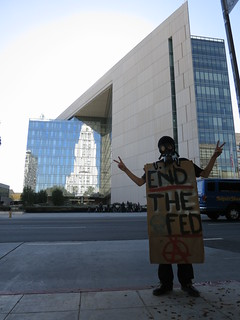 Occupy LA demonstrator in front of LAPD headquarter & line of bicycle cops