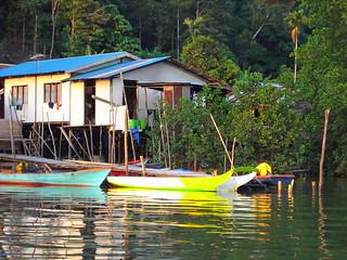 Fishing village on water front in Sarawak near Kuching in Malaysia. On the island of Borneo. Houses on stilts above water.Colourful boats reflected in the sea.