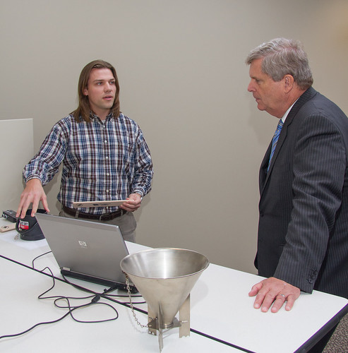TSD engineer Jason Jordon demonstrated to Secretary Vilsack the proper method for leveling off grain in the kettle used to measure test weight.