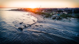 Image of Sandy beach. ocean city trees sea people beach dock waves aerial urbanexploration ladnscape runinng