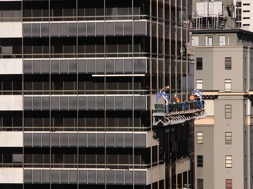 Installing steel mesh panels on the facade of 447 Collins Street