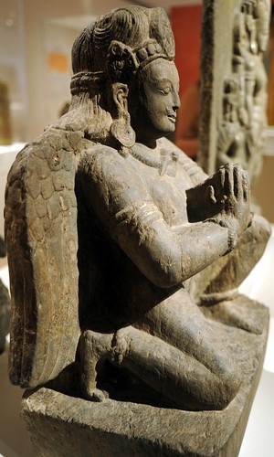 Statue of Vajra Guruda, kneeling winged male figure with headdress, crown, jewels, earrings, snake necklace, stone, hands clasped in prayer mudra, Chicago Art Institute, Chicago, Illinois, USA by Wonderlane