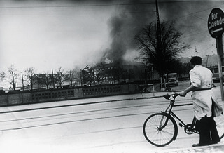 Cyclist looking at the burning Shellhouse (Getapo's head quarter) after the RAF attack.. 18th April 1944.