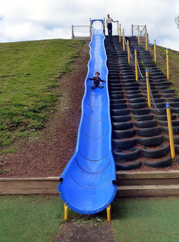A tiny boy on a big slide