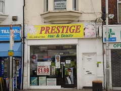 "A small terraced shopfront with a sign above reading ""Prestige Hair & Beauty"". A photo of a light-skinned woman's face is on the right-hand side of the sign, and a photo of a pair of light-skinned hands with long fingernails of on the left. The shopfront is divided into a larger fully-glazed half and a smaller half just a little wider than a door, clearly leading to the upper floors of the building. The shop windows are filled with posters showing women of various skin hues, as well as one advertising ""Threading £1.99"" in large letters. A sign reading ""Barzinji Accountancy Services"" is visible in the first-floor window."