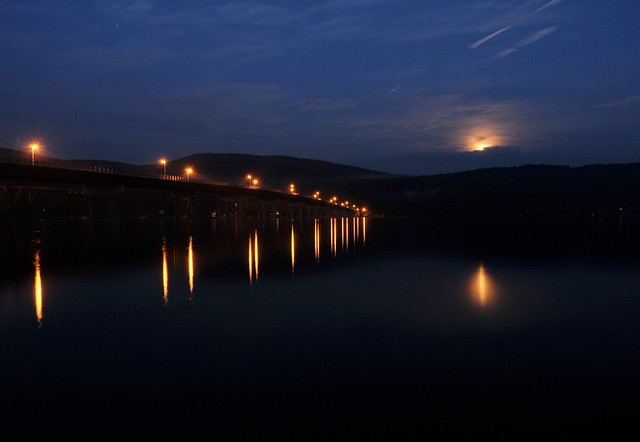 10pm as the just-past-full moon rises over the Great Sacandaga Lake. Lights from the new Batchellerville Bridge shine on the glassy waters. Have a listen.