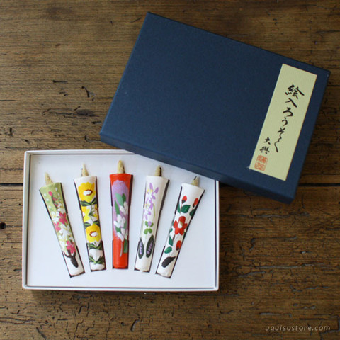 The candles are long and decorated with flowers in a fancy box