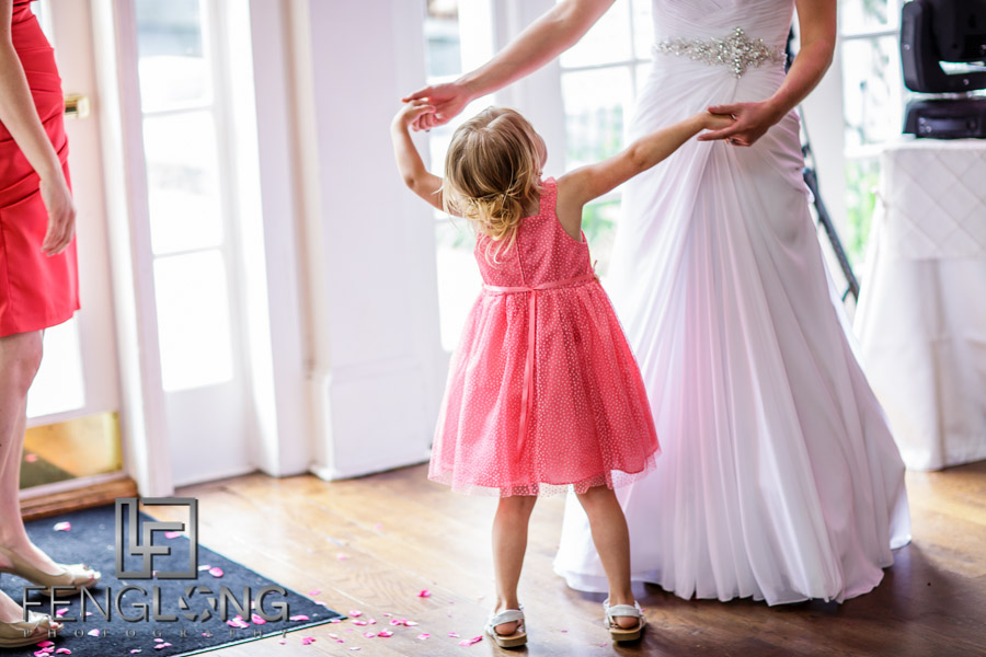 Bride dances with flower girl at wedding reception