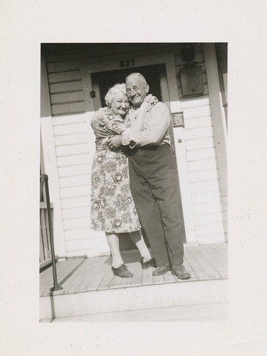 Affectionate elderly couple hugs on the porch