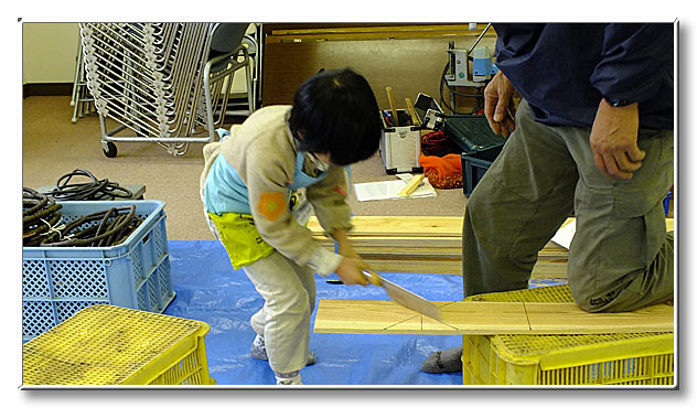 こちらは巣箱作り.先生と力を合わせて板材を切る.