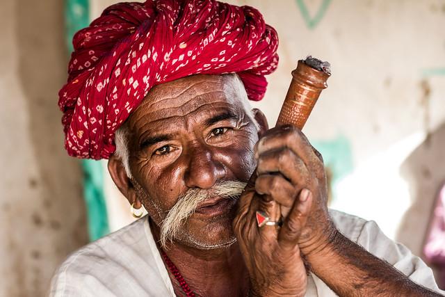 Old Rajput man with turban smoking pipe