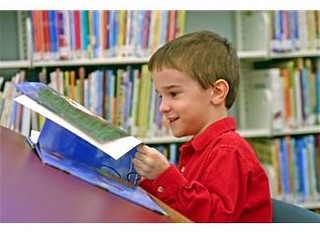 6 year old boy reading book in library