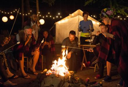 The project runway crew roasting marshmallows in a fancy campsite