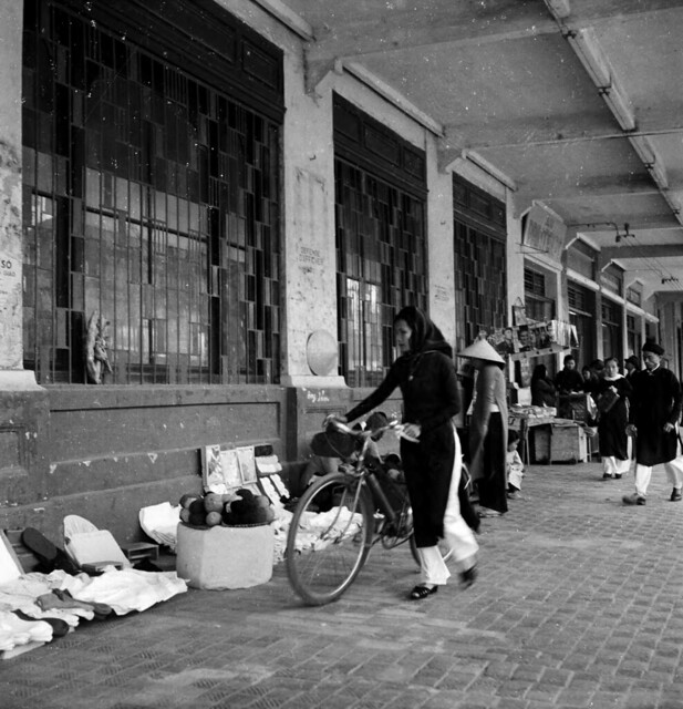 Hanoi 1950 - Woman with bicycle reviewing vendor's items for sale