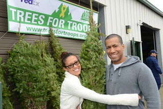 Petty Officer 3rd Class Roman Chavez, a Coast Guardsman at Training Center Cape May, N.J., poses with his wife, Karin, after receiving a donated Christmas tree from Trees for Troops Dec. 6, 2013. More than 50 Coast Guardsmen at Training Center Cape May and its 13 tenant commands received trees as part of the Trees for Troops program. (Coast Guard photo by Seaman Jennifer Nease)