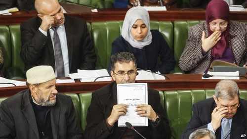 "A Tunisian parliament member holds up a copy of a document that reads in Arabic and the ""draft constitution for Tunisia. The country is attempting develop a governing document three after the removal of Ben Ali. by Pan-African News Wire File Photos"