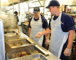 Lt. Cmdr. Chad Brick with the Coast Guard Seventh District prepares fish at the Chapman Partnership homeless assistance center in Miami, Jan. 17, 2014. The homeless assistance center provides support programs that include emergency housing, meals, health and psychiatric care. (U.S. Coast Guard photo by Petty Officer 3rd Class Mark Barney)