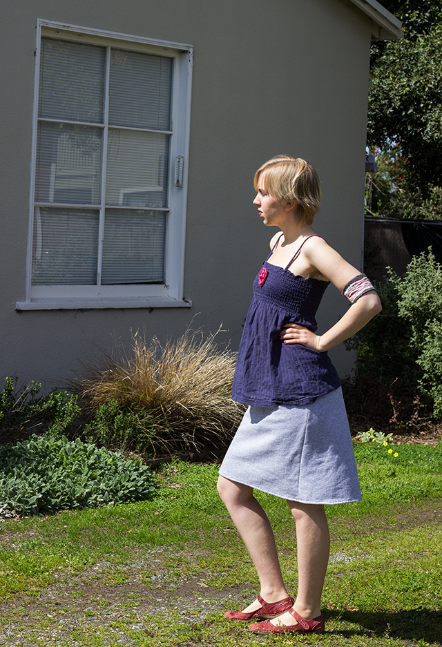 navy blue tank top with pink silk rose brooch, simple grey skirt