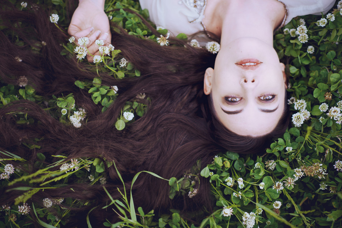 Gestalta photographed by Akiomi Kuroda. Long haired girl lying in grass, with white flowers, Japan