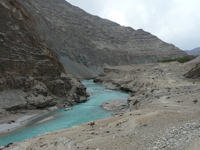 The Indus flows through a near-lunar landscape of grey-brown rocks and sand