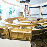 c01 -- JULY: Workers install the horseshoe-shaped desks in a classroom in State Farm Hall.