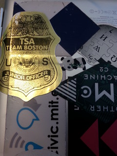 "A gold sticker replicates a TSA-agent's badge and reads ""TSA Team Boston, Junior Officer"" with the Department of Homeland Security emblem and eagles all over the place."