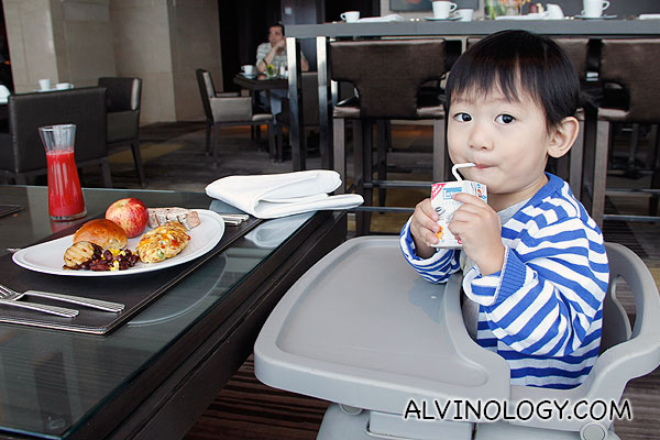 Asher enjoying his breakfast in a baby chair