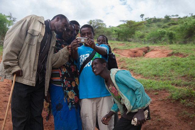 A pastoralist family checks their photo. Borana, Ethiopia (photo credit: ILRI\Zerihun Sewunet).