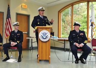 Rear Adm. Michael Parks, former commander of the Coast Guard 9th District, shares a story about Chief Petty Officer Michael Dugas (right) during Dugas' retirement ceremony at the Willoughby Hills Community Center in Willoughby Hills, Ohio, Sept. 30, 2013.Dugas retired after a combined 26 years of service in the Navy, Navy Reserve, Coast Guard and Coast Guard Reserve.U.S. Coast Guard photo by Chief Petty Officer Kyle Niemi