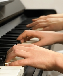 Image of four hands playing a piano