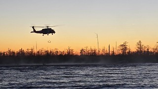 Coast Guard Air Station Elizabeth City aircrew aboard an MH-60 Jayhawk helicopter rescued three people and a dog Dec. 18, 2013, after their 23-foot boat ran aground in the shallow waters at the mouth of the Alligator River near Elizabeth City, N.C. (U.S. Coast Guard photo by Fireman Jeremy Ellard)