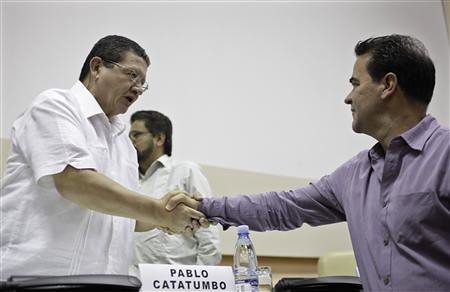 FARC negotiator Pablo Catatumbo, left, shakes hands with Colombian government negotiator Frank Pearl during talks in Havana, Cuba on May 26, 2013. The talks have been taking place for several months. by Pan-African News Wire File Photos