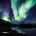 Northern lights over mountains and calm lake by @ilovegreenland