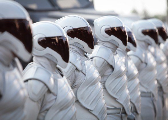 Peacekeepers in Catching Fire wear face shieids and stand in a long line