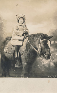 Child in a winter coat sitting on a pony
