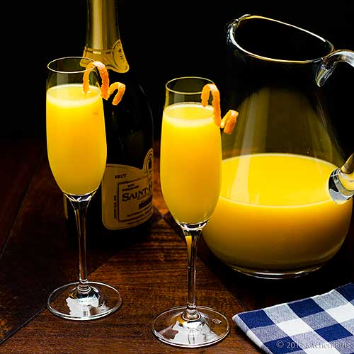 Mimosa Cocktails with orange twist garnish, champagne bottle and pitcher of orange juice in background