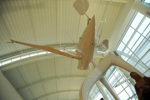 Space Observer by artist Björn Schülke, alien technomodern three legged, white sculpture, embedded camera, woman with handheld device, San Jose International Airport, California, USA by Wonderlane