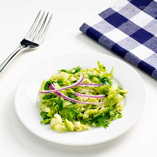 Hashed Brussels Sprouts with red onion garnish on plate, with fork and napkin in background